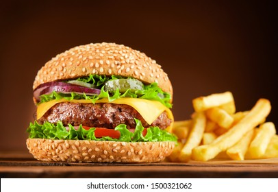 fresh cheeseburger with french fries on wooden table