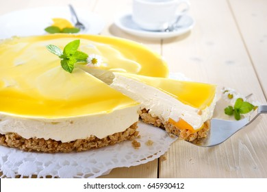 Fresh cheesecake with mango fruit and glaze, the flan case made of cookie crumbs