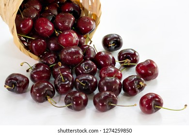 Fresh cherries in bamboo basket and fall out frome basket on white background / Select focus, space for texts