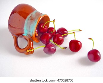 Fresh cherries in a cup lying on white table