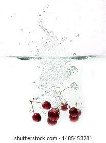 fresh cherries falling in water on a white background