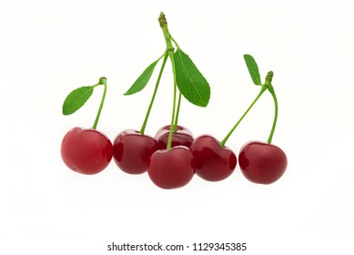 Fresh cherries with green leaves isolated on white background.