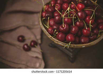 Fresh Cherries on an Antique Scale; Low-Key Warm Brown Background