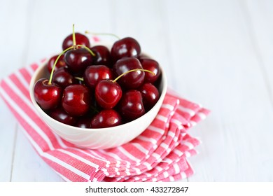 Fresh Cherries in a white bowl on white table