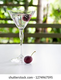 Fresh Cherry in glass with soda water which has another one cherry  put on white floor table in green garden / Blurred and Select focus and space for texts