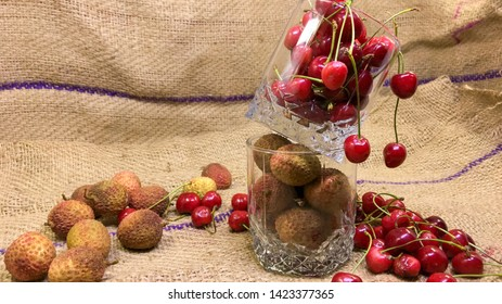Fresh cherry and Fresh litchi fruit on burlap and Sackcloth texture background. fresh ripe cherries and litchi fruit. sweet cherries.