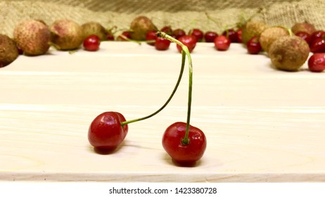 Fresh cherry and Fresh litchi fruit on burlap and Sackcloth texture background. fresh ripe cherries and litchi fruit. cherry and lirchi on wodden background.