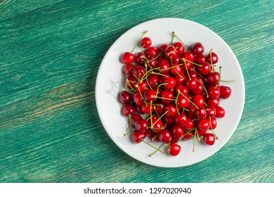 Fresh cherry on plate on wooden green background. fresh ripe cherries. sweet cherries. Flat lay or top view.