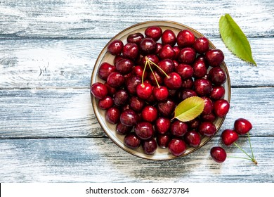 Fresh cherry on plate on wooden blue background. fresh ripe cherries. sweet cherries.