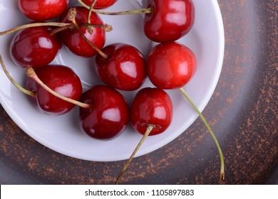 Fresh cherry on wooden plate. fresh ripe cherries. Top view. sweet cherries.