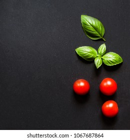 Fresh cherry tomatoes and basil leaf  on black slate stone chalkboard with copyspace. Healthy Italian traditional caprese salad ingredients. Organic Mediterranean food concept, flat lay