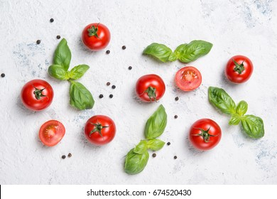 Fresh cherry tomatoes with basil leaves and black pepper on a stone table, vegetable pattern, top view