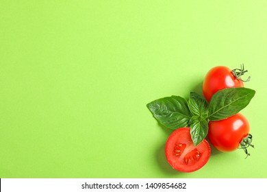 Fresh cherry tomatoes with basil on color background, space for text. Ripe vegetables