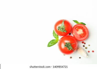 Fresh cherry tomatoes with basil, pepper and garlic on white background, space for text and top view. Ripe vegetables