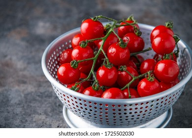 Fresh cherry tomatoes in colander.