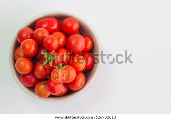 Fresh cherry tomatoes are in a cup on a white background.