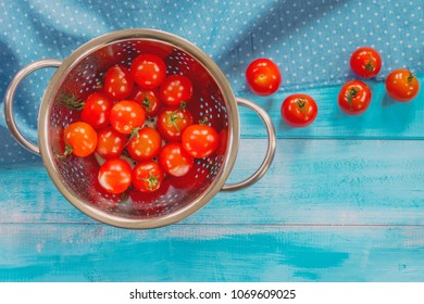 Fresh cherry tomatoes with drops of water in a colander. The cherry tomatoes on a blue background. Cherry tomatoes top view.