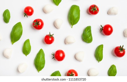 Fresh cherry tomatoes, cherry mozzarella, fresh basil on white background, top pattern. Top view.