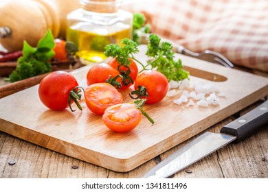Fresh cherry tomatoes with olive oil on table.