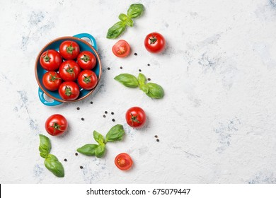 Fresh cherry tomatoes on a plate, basil leaves and black pepper on stone table, top view