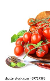 Fresh cherry tomatoes on plate, spoon and fork