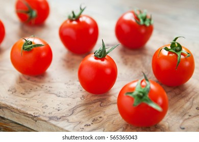 Fresh cherry tomatoes on a wooden background. Top view with copy space.
