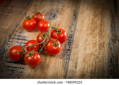 Fresh cherry tomatoes on wooden background, France