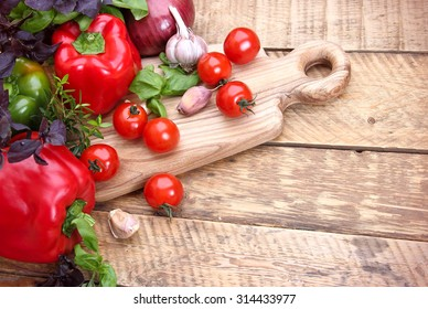 fresh cherry tomatoes, peppers, garlic, onion on a wooden background