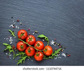 Fresh cherry tomatoes, salt, pepper and arugula leaf on a black slate board, top view