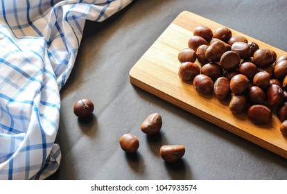Fresh chestnuts on dark black rustic background. Pile of fresh chestnuts ready to roast shot over black antique background. Top view.