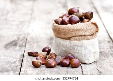 fresh chestnuts in sack bag on the old wooden table