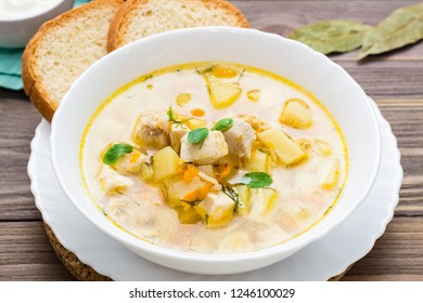 Fresh chicken broth soup with potatoes and herbs in a white bowl on a wooden table