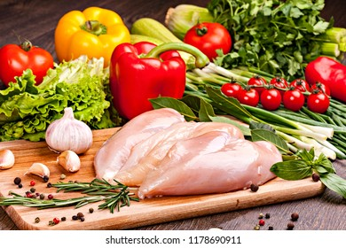Fresh chicken meat for cooking  with vegetables, spices and herbs. Close-up on cutting board.