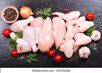 fresh chicken meat on dark board, top view.