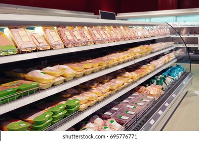 Fresh chicken meat on supermarket shelf, all logos removed, toned image