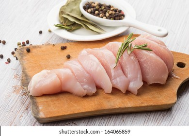 Fresh chicken meat on wooden board on white table. Selective focus. Rustic style.