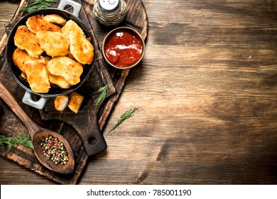 Fresh chicken nuggets with sauce and spices. On a wooden table.