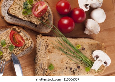 Fresh chicken pate with vegetables and herbs on a wooden chopping board