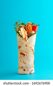 Fresh chicken roll with fresh tomatos, salad, cheese and onions isolated on bright blue background. Side view.