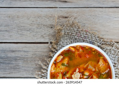 Fresh chicken soup with vegetables on wooden table. Lunch time.