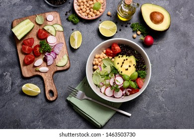 Fresh chickpea and lentil salad with  black lentils, veggies and avocado, cutting board with cut vegetables, vegan lunch bowl or healthy snack, clean eanting and detox food concept