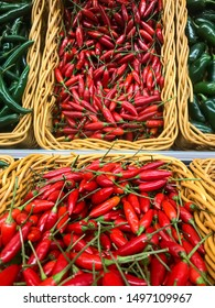 Fresh chillies variety piled in the baskets on the market. Birdseye chillies with some Green Cayenne and Jalape?o peppers on sides. Food background. Harvest
