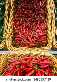 Fresh chillies variety piled in the baskets on the market. Birdseye chilli. Food background. Harvest