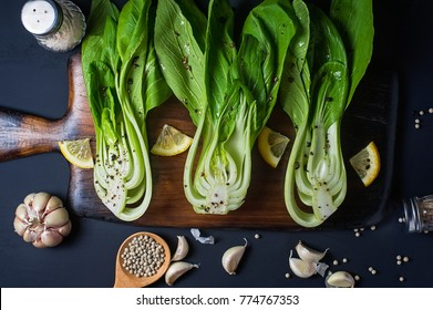 Fresh Chinese cabbage or Bok Choy with lemon slice and pepper on blue dish