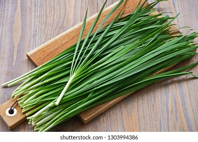 Fresh Chinese Chive or Kui-chai tie a rope on wooden board. Healthy and benefits of Garlic chives.
