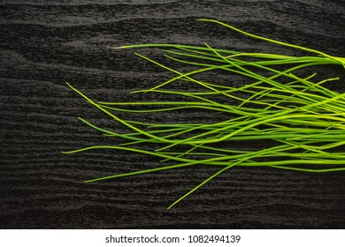 Fresh chives top view isolated on black wood background grass-like leaves fines herbes