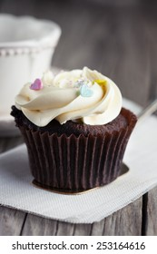 Fresh chocolate cupcakes decorated with creamy vanilla cream on old wooden background, selective focus