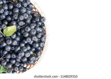 Fresh chokeberry or Aronia melanocarpa in basket, isolated on white background. Top view. Design element.