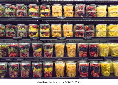 Fresh chopped and chunks fruits plastic cup display in store. In-house cut and packed mixed berries, kiwi, mango, cantaloupe to take away. Convenience, healthy lifestyle.  Colorful slices background.