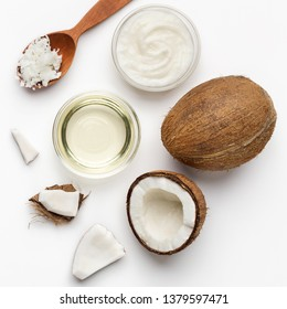 Fresh chopped coconuts, coco flesh and bowls of coconut oil on white background, top view. Coconut body care concept